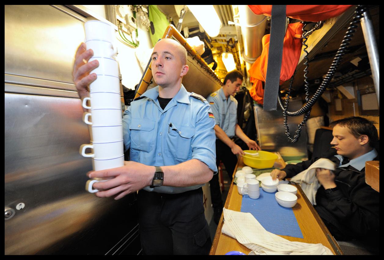 Nach dem Frühstück steht das Abwaschen auf der Tagesordnung. Wohnen, schlafen und essen auf engstem Raum. An Bord der U-17 herrscht der Zweischicht-Betrieb: Je zwei Männer teilen sich eine Koje und arbeiten und schlafen im Wechselbetrieb.