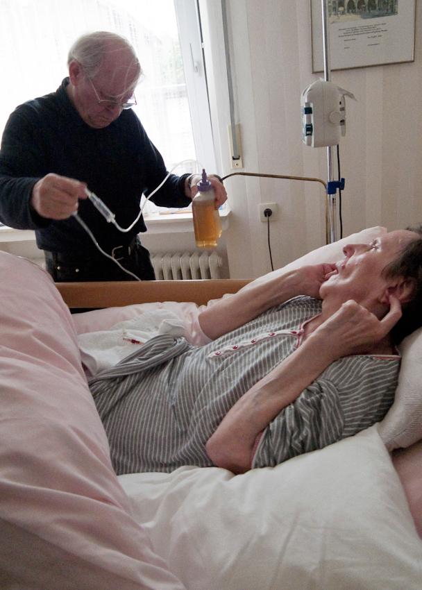 Ein Tag Deutschland, 07.05.2010, 59329 Wadersloh, NRW: 80 jähriger Mann pflegt seine an Multisystematrophie (MSA) erkrankte palliative 77 jährige Frau zu Hause.  Ein Behälter mit Kamillentee wird an die Magensonde angeschlossen.