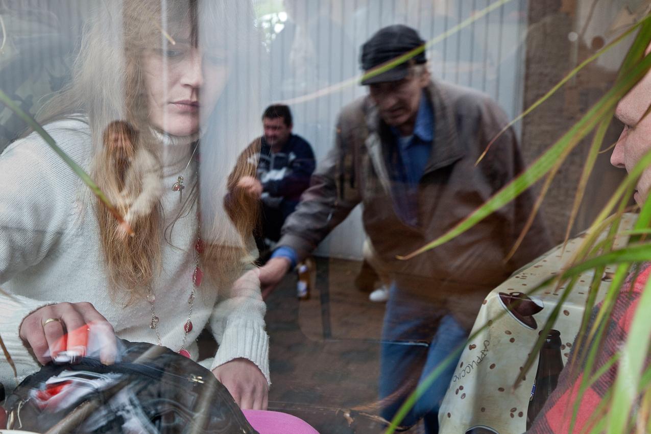 """Herford: Bevor der Mittagstisch öffnet, trifft man sich im Tagesaufenthalt des """"Sozialberatungsdienstes"""". Tanja unterhalt sich drinnen mit Jörg, während draußen gerade Wolfgang ankommt. Vor der Garage sitzt (links) Wasili und wartet auf seinen Termin mit dem Sozialarbeiter Jochen. Projekt A: Herforder Mittagstisch e.V., Medizinische Hilfe für Bedürftige e.V., Sozialberatungsdienst. Ehrenamtliche Helfer der Herforder Petri-Gemeinde bewirten seit über 10 Jahren bedürftige Menschen jeden Tag an einem gedeckten Tisch. Im gleichen Haus sitzen auch die Profis des Sozialberatungsdienstes. Einmal die Woche bieten ehrenamtlich arbeitende  Ärztinnen Sprechstunden an."""