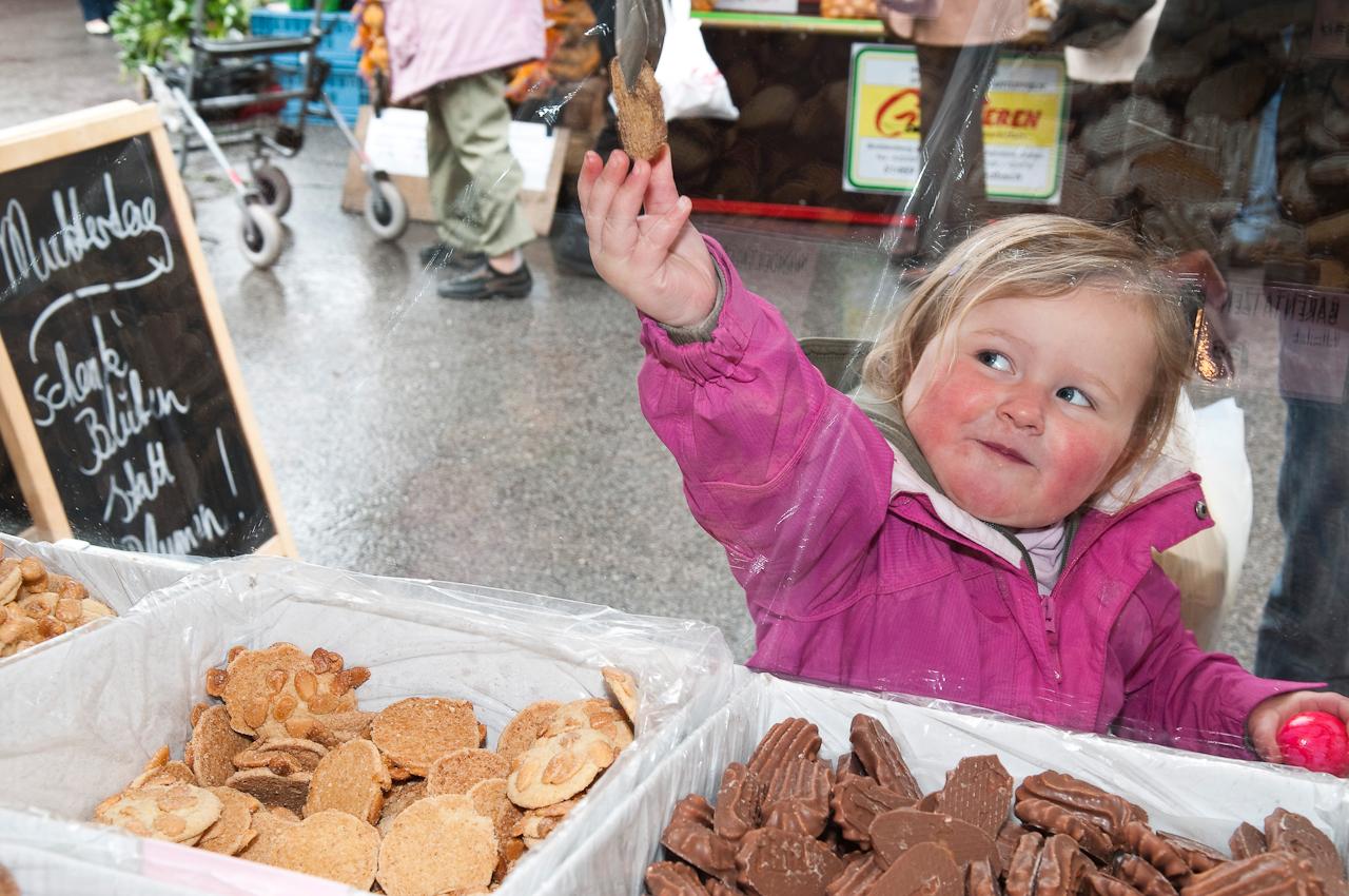 """Wochen-Markttag in Refrath, Bergisch Gladbach, am 7.5.2010, fotografiert von Ulla Franke. Mia reckt den rechten Arm, um den ihr von oben zugereichten Keks bei """"Zimt & Zucker"""" zu erhalten."""