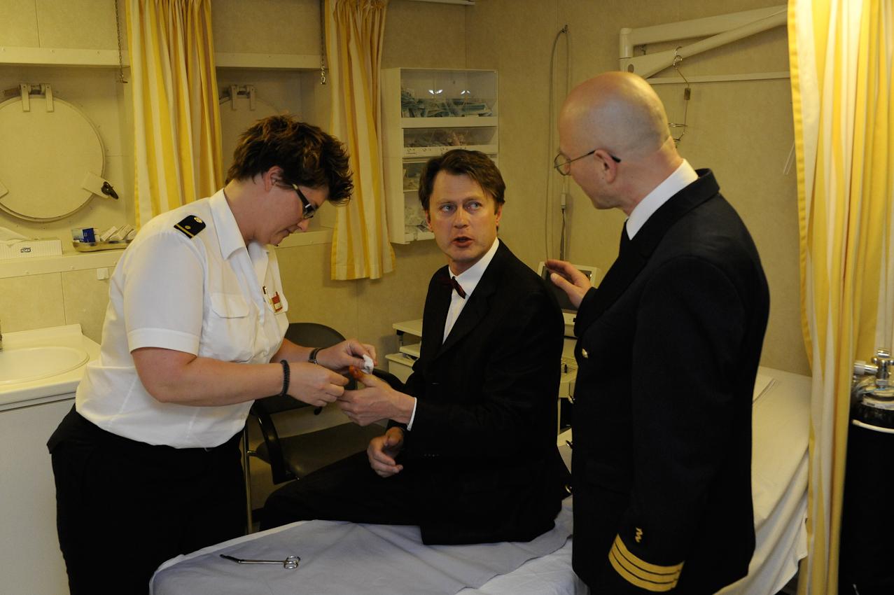 Auf dem Kreuzfahrtschiff MS Deutschland. Passagier wird im Bordhospital vom Schiffsarzt und Krankenschwester verarztet.