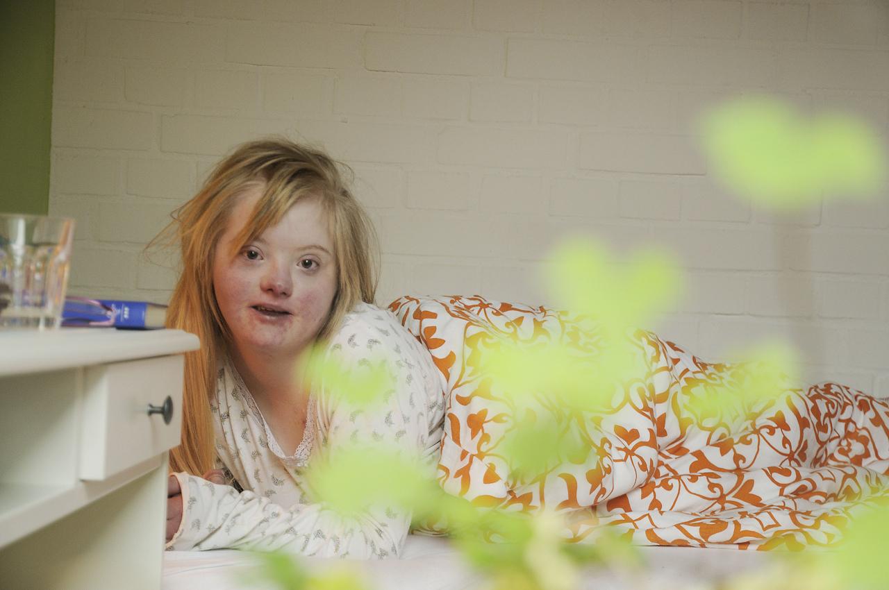 Keke, eine junge Frau, 18 Jahre, lebt mit dem Down-Syndrom (Trisomie 21). Die Familie versucht ein normales Leben zu führen. Keke ist meist gut drauf, selten erlebt man sie traurig oder verzagt. Sie nimmt das Leben wie es ist. Auf dem Foto ist aufstehen angesagt.  Anbei Text über Keke von ihrer Schwester: In unserer schnelllebigen Gesellschaft, in der oft die essentiellen Dinge aus den Augen verloren werden ist Keke ein Mensch, der zeigt was das Leben bedeutet. Denn Ihres ist das kostbarste Gut. Welch Glück hatte meine Familie, dass uns solch ein Schatz in die Mitte gelegt wurde. Unsere Keke. Ihre offene Art verwirrt die Einen und bezirzt die Anderen. Sie hat unschlagbare Argumente und ihre Frechheit macht mich stolz. Sie kokettiert mit den Erwartungen Anderer an sie und erspürt zwischenmenschliche Zusammenhänge. Sie hat einen unendlichen Schatz an Erinnerungen und ist ein großer Film-Fan. Die Lehrer dachten, der Sprachunterricht wäre umsonst, doch wenn sie will, dann spricht sie Englisch. Sie freut sich über Kleinigkeiten, weil sie wichtig sind und ist schrecklich geduldig. Sie ist eine wunderbare Tänzerin und sehr elegant. Wenn wir uns um ihre Gesundheit sorgen, versteht sie sich darauf uns zu trösten. Ich glaube, sie kann mit Tieren sprechen. Sie liebt ohne Kompromisse und erwartet keine Gegenleistung für ihre Zuneigung. Unsere Keke. Meine wunderbare Wunderschwester.