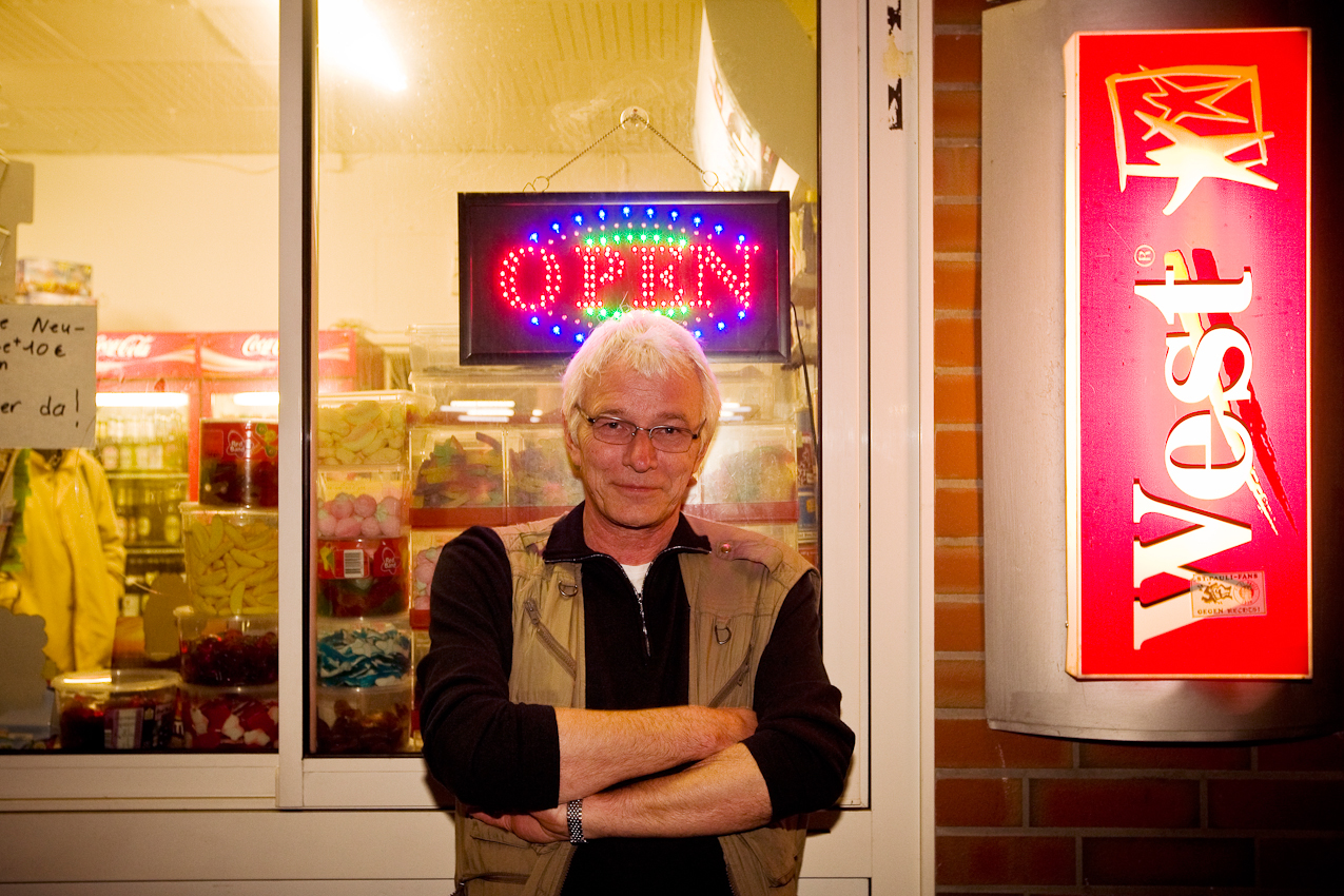 Der Fotograf Christoph Keller vor einem Kiosk am Vogelhuettendeich. Trotz der spaeten Uhrzeit immer noch 'open' fuer Wilhelmsburg.