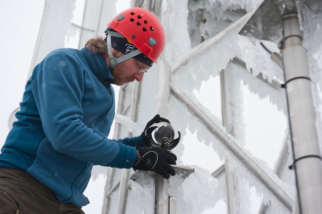 Wo kommt das Wetter her? - Ein Tag mit dem Wetterdiensttechniker Rene Sosna auf dem Brocken.  Der Wetterdiensttechniker Rene Sosna beim Einrichten des Sonnenscheinautographen nach Campbell & Stokes auf einer Plattform, nachdem er sie vom Eis befreit hat. Im Hintergrund sieht man den Windmasten auf dem Dach der Wetterwarte Brocken, der von dem Eisregen der vergangenen Nacht stark mit Eis bedeckt ist.