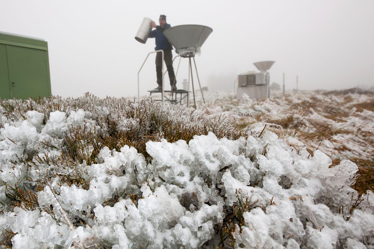 Der Gebirgsniederschlagsmesser wird alle 6 Stunden routinema?ig gewechselt.  Ein Regenwassersammelbehälter wird wieder in eine Sammelstelle gestellt. Durch den Eisregen der vorhergegangenen Nacht ist der Boden und sind die Büsche vereist.