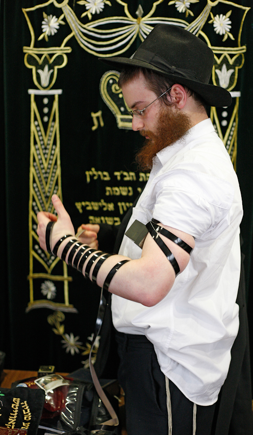 Nach dem Besuch der Mikwe geht Jehoshua Berkovicz in die Yeschiwa, um dort sein Morgengebet zu verrichten. Zum Ritual gehört das Anlegen der Tefillin, der jüdischen Gebetsriemen. Sie bestehen aus zwei Teilen, einem Riemen für den Kopf und einem für den Arm. In den schwarzen Kästchen sind auf Pergament geschriebene Bibelverse.