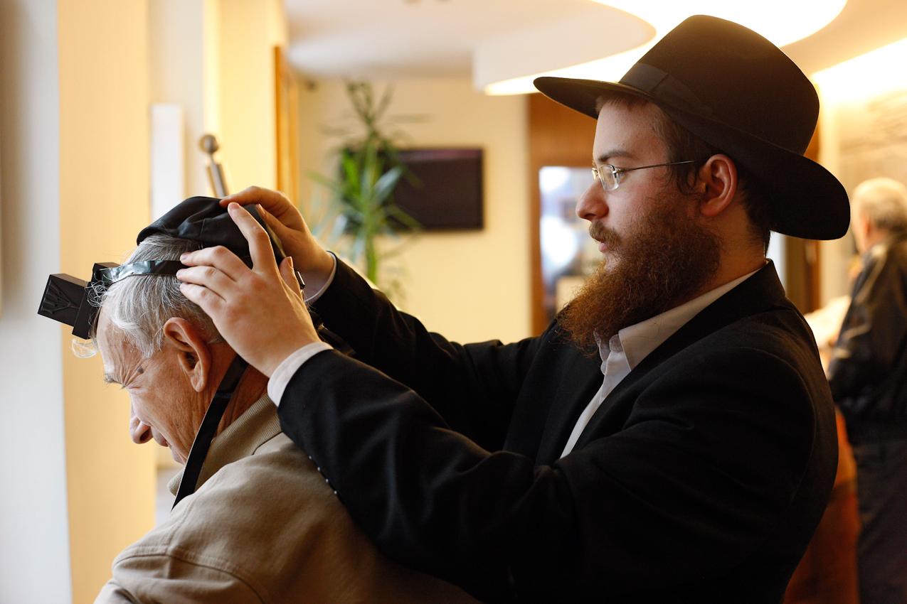 Nach dem Morgengebet hilft  Jehoshua Berkovicz im Jüdischen Bildungszentrum in der Berliner Münsterschen Straße anderen Besuchern beim Anlegen der Tefillin und spricht mit ihnen einen Segen. Dieses Ritual soll unter anderem einen besonders schnellen Weg zu Gott und zueinander ermöglichen.