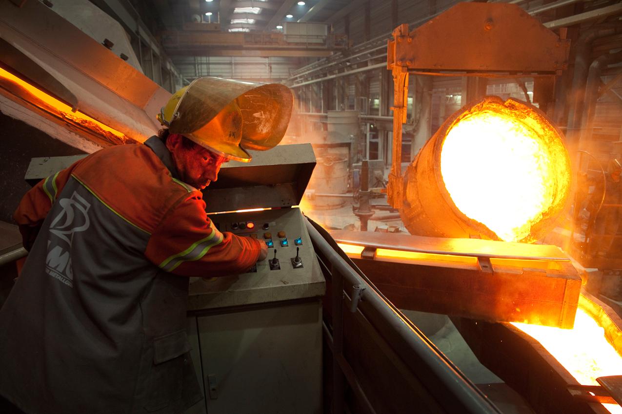 Aus zwei Behältern wird das glühende Gussmaterial über die Einfüllrinne in die Gussform des Propellers gegossen. Der Arbeiter am Ofen beobachtet konzentriert den Fluss des Gussmaterials in der Rinne.