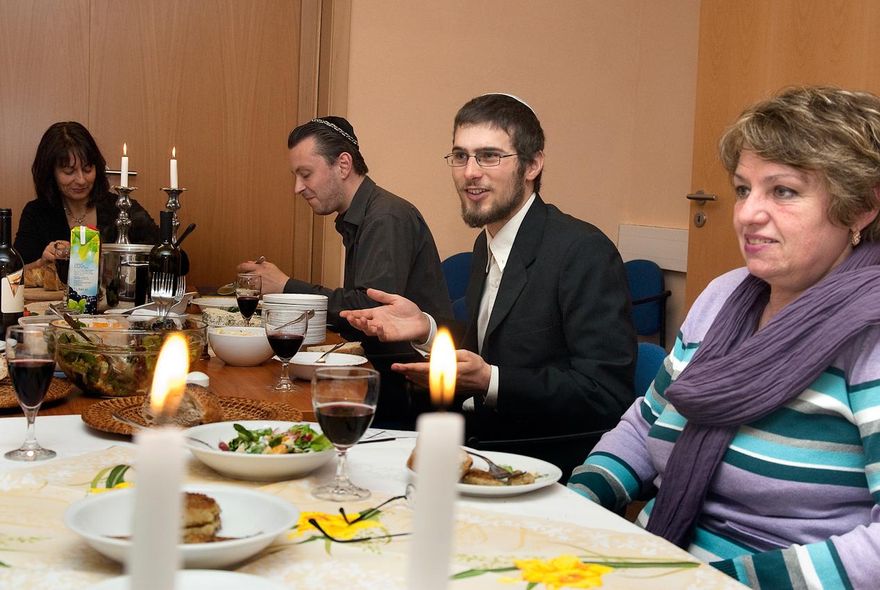 <p>Mitglieder der jüdischen Gemeinde in Göttingen treffen sich am Freitagabend im Gemeindehaus gemeinsam mit Gästen zum Schabbes-Mahl. Nachdem die Kerzen entzündet sind, spricht die Vorsitzende der jüdischen Gemeinde, Jacqueline Jurgenliemk, den Segen über dem vollen Becher Wein. Sie schneidet die mit einem bestickten Tuch bedeckten Sabbatbrote an und reicht die Brotscheiben mit Salz weiter. Die jüdischen Gemeindeangehörigen feiern den Beginn des Sabbats mit Essen, Trinken und Plaudern in fröhlicher Runde.</p>