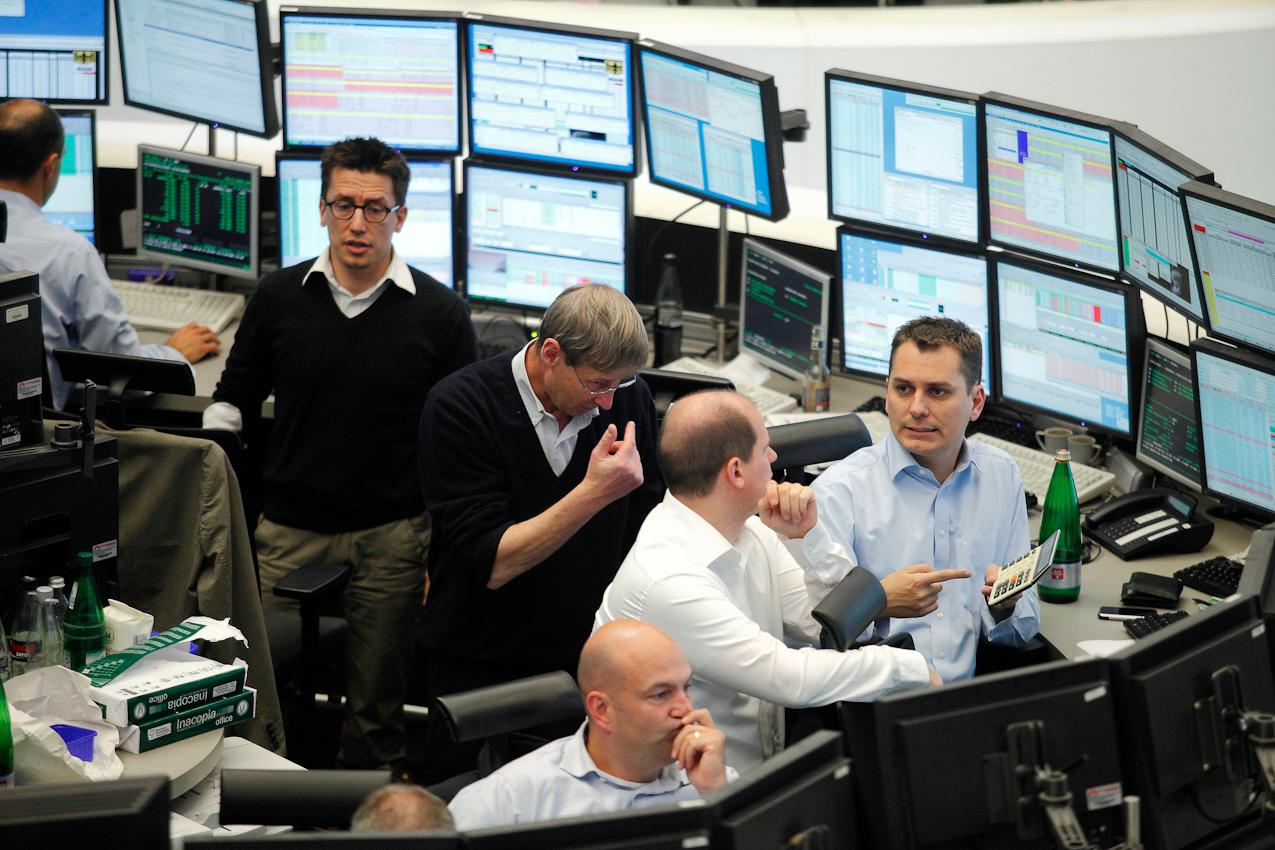 """Broker und Wertpapierhändler beim Aktienhandel auf dem Parkett im Handelssaal der Deutschen Borse AG.  Die Vorgaben aus New York waren miserabel. Tags zuvor am Donnerstag brach der Dow Jones Index der amerikanischen Leitbörse auf rätselhafte Weise um 1000 Punkte ein, verursacht entweder durch einen ,,bad finger"""" Tippfehler eines Händlers oder durch computergesteuertes Algo-Trading. Die Frankfurter Aktienhändler gingen also mit sehr gemischten Gefühlen an diesem Freitag zur Arbeit. Zunächst sah alles auch ganz gut aus, aber im Laufe des Tages spitze sich die Lage abermals zu. """"Die spinnen, die Amis"""", schimpfte ein Händler. """"Wir wehren uns hier gegen Attacken der Day-Trader."""" Am Nachmittag brach regelrechte Verkaufspanik auf dem Parkett aus. Der Dax befand sich im freien Fall. Den Händlern stockte der Atem. Stress pur in den Gesichtern. Am frühen Abend  kollabierte  der Computerhandel an der Frankfurter Börse und wurde für gut zehn Minuten ausgesetzt. """"So etwas habe ich hier noch nie erlebt"""", staunte ein Broker. Die Händler diskutierten ratlos. Sie hatten ihre Bücher voller Verkaufsorders, die sie nicht ausführen konnten. Dann ging es weiter. Warum der Handel unterbrochen wurde, wusste hier niemand. Jeder war froh, als dieser verrückte Handelstag vorbei war."""