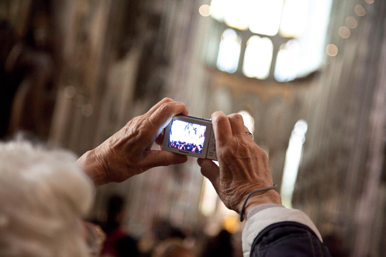 Ältere Frau fotografiert das Innere des Domes mit einer digitalen Kamera.