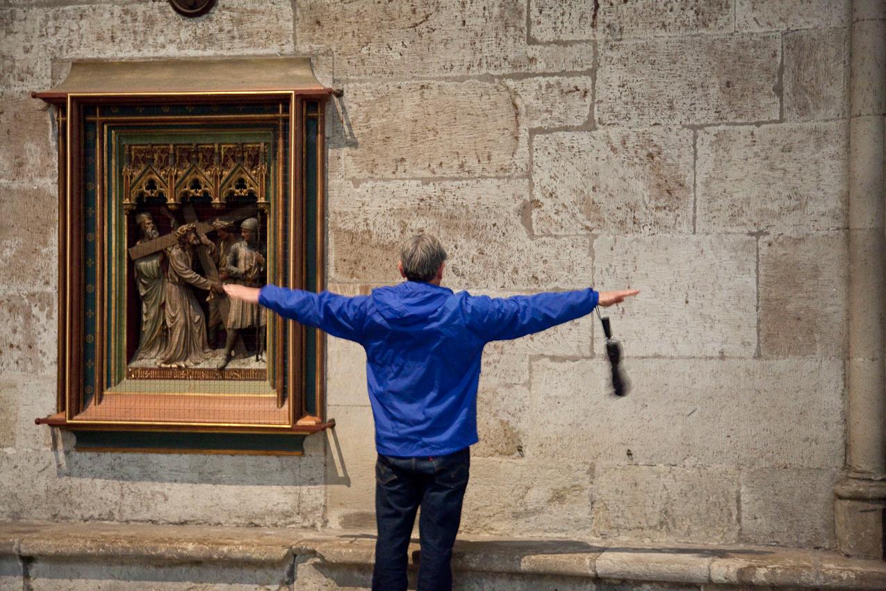 Kreuzweg, 3. Station, 1. Fall Christi. Ein Besucher misst mit seinen Armen die Breite der Fenster nach.