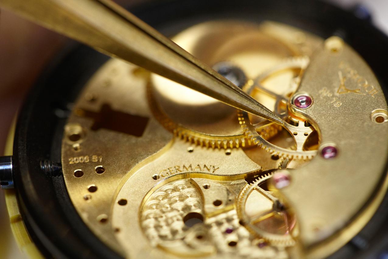 """Volker Vyskocil prüft um 13:17 Uhr mit der Kornzange das Minutenrad des Werkes der von ihm gebauten Armbanduhr """"VA"""". Es handelt sich um die laufende Nr. 19 seiner ersten Baureihe."""