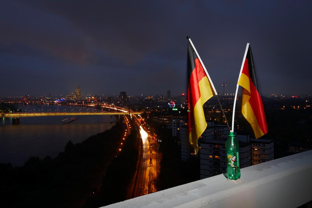 Balkon mit Deutschlandfahnen im Colonia-Hochhaus in Köln-Riehl um 21:35 Uhr mit Blick auf Rhein, Zoobrucke und Dom.