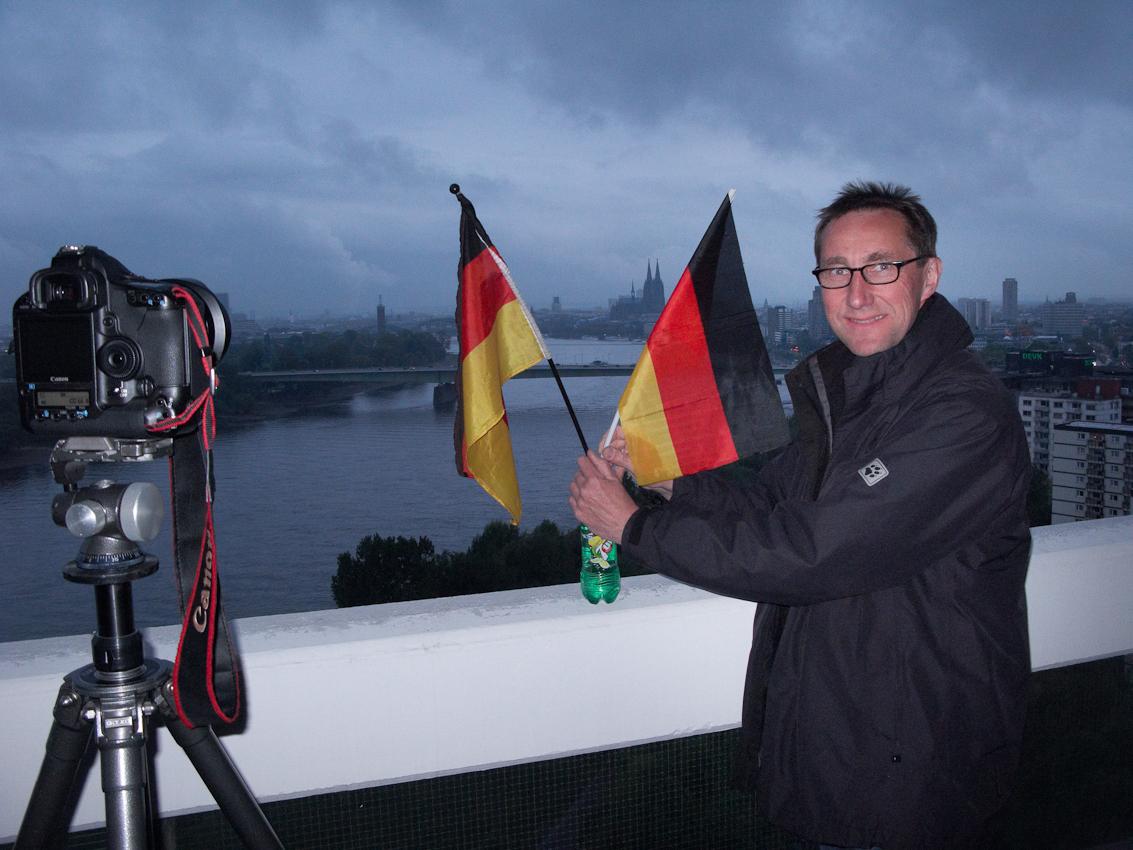 Um 20:53 Uhr richtet Ralf Baumgarten die Deutschlandfähnchen für die Aufnahme des Kölnpanoramas vom Colonia-Hochhaus in Köln-Riehl aus.