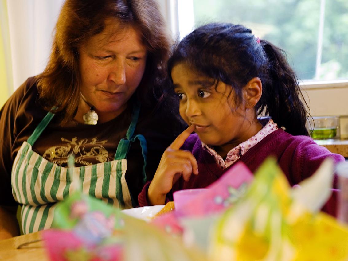 """Ersatzmutter: Hajerah ist mit Zahnschmerzen aus der Schule gekommen. Haushaltshilfe Irene, die eigentlich """"nur"""" fur das Kochen zuständig ist, hort sich ihre Sorgen an. Finanziert wird ihre Stelle als Wiedereingliederungsmaßnahme von der Arge.  Der Hort, Dieselstraße 1, in Herford besteht seit 1989  als sozialpädagogische Tageseinrichtung fur Grundschulkinder. 2007 wurde er im Rahmen der Kampagne """"Deutschland Land der Ideen"""" vom Bundespräsidenten zu einem von 365 """"ausgewählten Orten. Bis 2008 unterlag der Hort dem Gesetz uber ,,Tagesstätten fur Kinder"""" (GTK), im seitdem in Nordrhein-Westfalen geltenden Kinderbildungsgesetzt sind Horte nicht mehr als Regeleinrichtungen erwähnt. Kommunale Sparzwänge bedrohen die Qualitat der Arbeit des vom lokalen Verein fur soziale Arbeit und Beratung getragenen Hortes zusätzlich."""