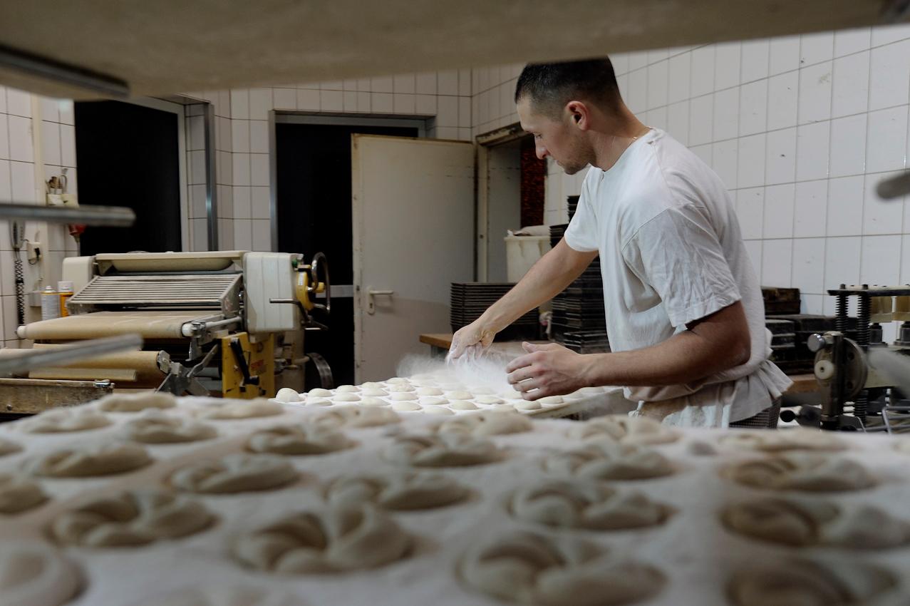Heßheim, Stadtbäckerei Frankenthal. Brötchenproduktion. Lukas Walter bestreut Teiglinge mit Mehl, damit diese nicht in der Formmaschine (ganz links) kleben bleiben. Im Vordergrund Teigformen fur Kaiserbrötchen.