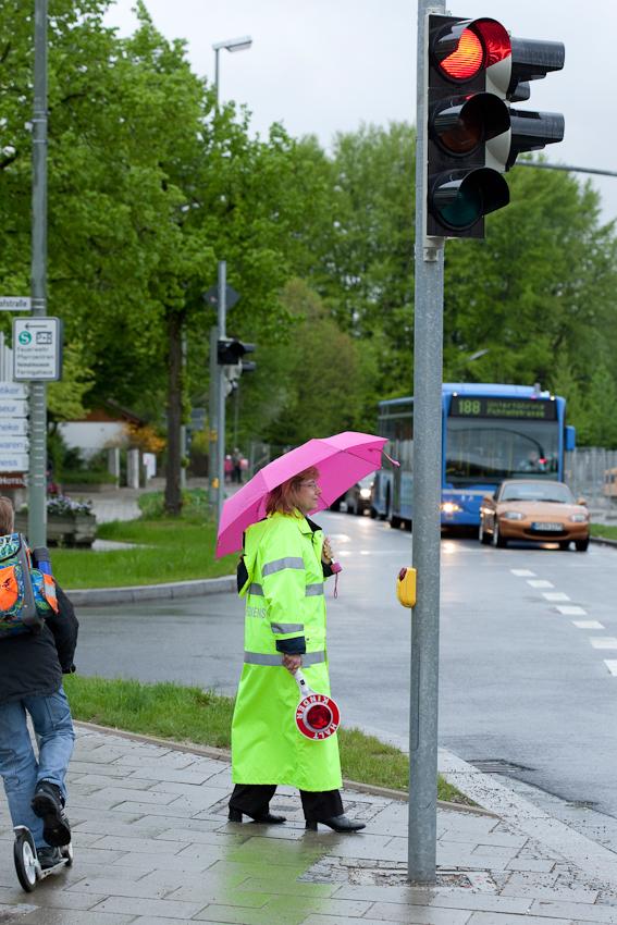 Mein Thema: Frühlingsgarten in Südbayern Aber es regnet dauerhaft.  Ich beschließe, erst mal einen Frühlingsbiergarten zu fotografieren. Auf dem Weg dorthin fällt mir diese Schulweghelferin in pink-gelb auf, die in Unterföhring bei München am tristen Morgen ein wenig Fröhlichkeit verbreitet.   Es ist 7.45, viele Schüler sind nicht mehr unterwegs,  die Schule beginnt um 8 Uhr.