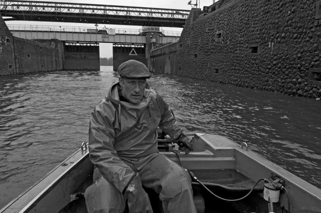 Elbfischer Olaf Jensen fährt im kleinen offenen Boot in die gewaltige Schleusenkammer der Rugenberger Schleuse. Der Fischer wartet in der Schleusenkammer bis die Tore sich öffnen und grünes Licht die Ausfahrt signalsiert. Er fährt er auf Fischfang im Hafenbereich und der Elbe. Dabei kommt er an grossen Containerschiffen, Terminals, und unter der Koehlbrandbruecke sowie zahlreichen Schleusen vorbei. Müdigkeit ist nach Stunden im Regen ein Problem. Jensen ist heute seit um vier Uhr unterwegs!