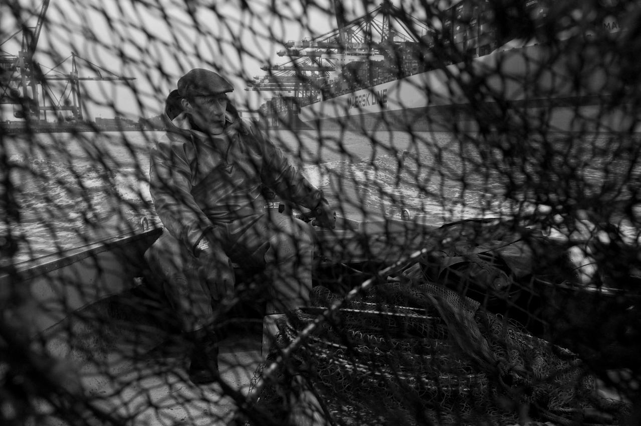 Blick durch die Maschen einer Aalreuse auf den Fischer Olaf Jensen fischt mit Aalreusen, im kleinen offenen Boot fährt er auf Fischfang im Hafenbereich und der Elbe. Dabei kommt er an grossen Containerschiffen, Terminal Eurogate sowie zahlreichen Schleusen vorbei. Heute ist ein Ausfalltag ohne jeden Fang. Der Regen fällt unaufhorlich und es kalt dazu. Seit vier Uhr ist Jensen unterwegs jetzt ist es gleich acht Uhr.