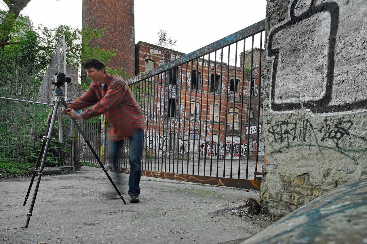 Darstellung des Fotografen Robert Conrad beim Ausrichten einer Kamera auf Stativ.