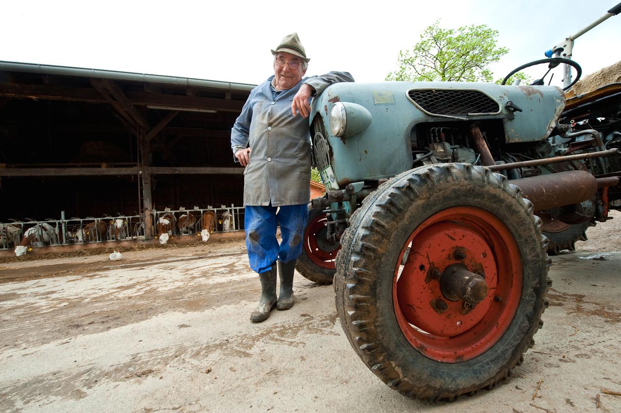 """Josef ist der Altbauer am Hof seines Sohnes. Ein """"gämütlicher"""" wie man in Bayern sagt. Freundlich und interessiert, immer für ein Schwätzchen zu haben. Allgemein bekannt im Ort und jeder der über ihn redet, tut es wohlwollend. Mit seinem museumsreifen Traktor leistet er noch immer ganze Arbeit am Hof - von Rentner keine Spur. Aber den Kredit, den sein Sohn für den neuen Hof aufgenommen hat, weil der alte Hof bei einem Großfeuer abgebrannt ist, den ist er froh nicht tragen zu müssen - sagt er.  Inning, 7. Mai 2010; 14:20 Uhr."""