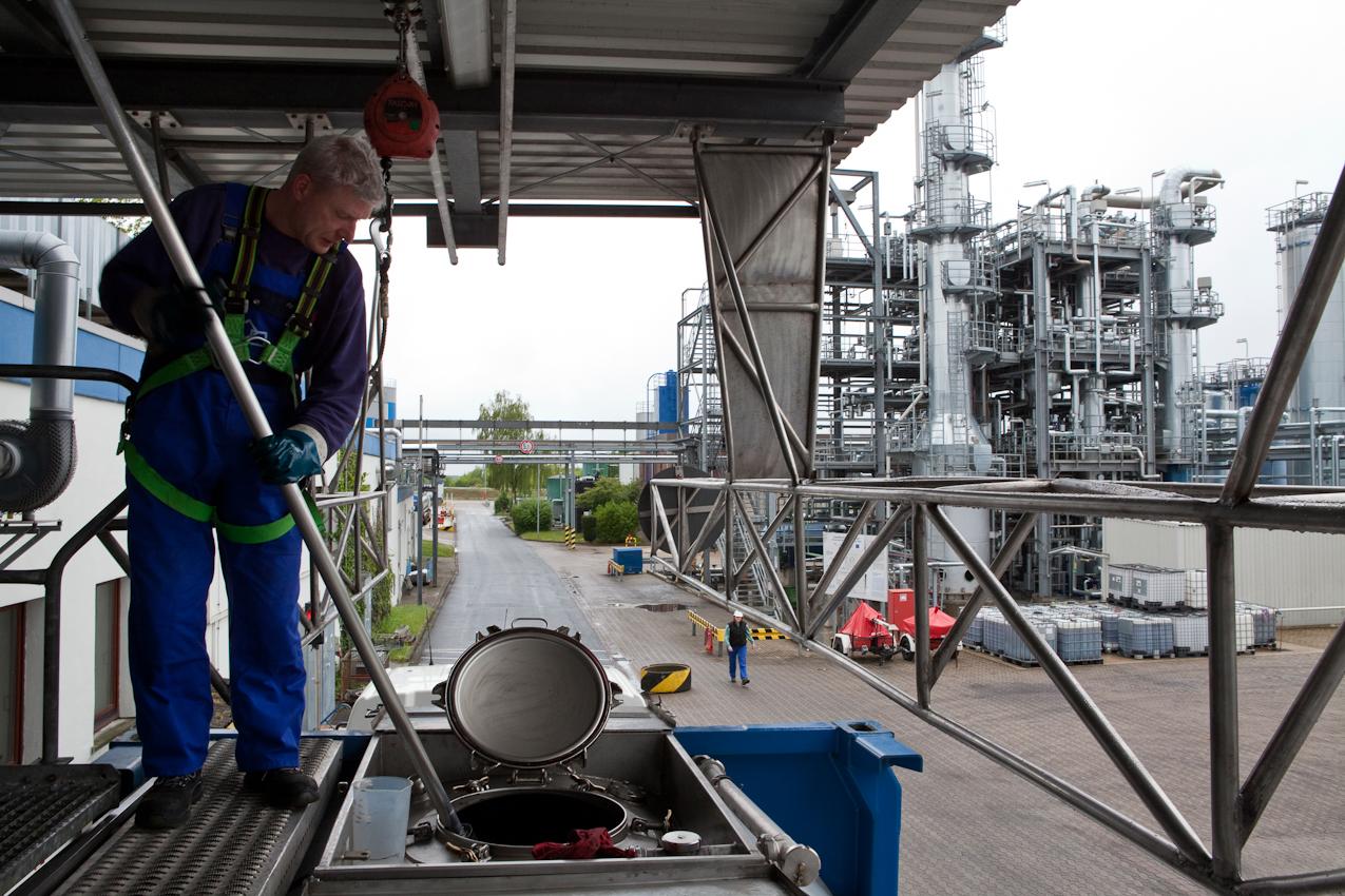 Bevor das Altöl entladen wird, entnimmt der Laborant Henner Meyer eine Probe zur eingehenden Untersuchung im Eingangslabor. Im Hintergrund ist das Herzstück der Raffinerie zu sehen, die Erweiterte Selektiv-Raffination.