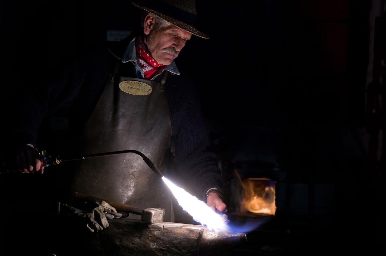 """Der Kunstschmied Lothar Klute bringt in seiner Schmiede in der Waldemai in Schmallenberg-Niedersorpe den Fühler fur eine seiner berühmten """"Riesenmücken"""" zunächst per Lötlampe auf die richtige Temperatur, bevor er zum Schmiedehammer greift.  - Dieses Bild wurde am 07.05.2010 um 11:16:45 Uhr in Schmallenberg-Niedersorpe (Sauerland, Deutschland) aufgenommen."""