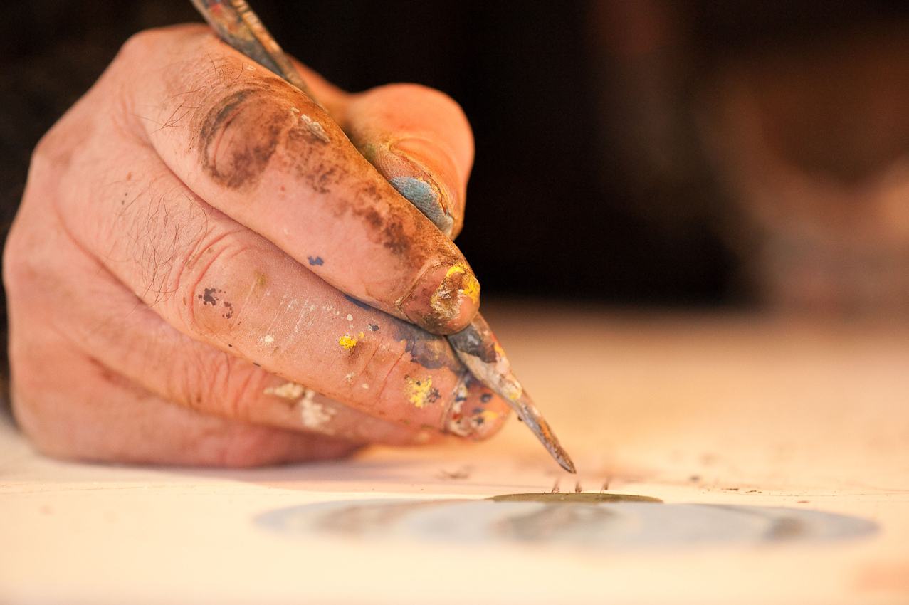 Die Hand des Künstlers schwebt uber dem Bild - der Maler Hans-Georg Bergenthal bei der Arbeit in in einem alten Speicher hinter dem Heimat- und Schiefermuseum in Schmallenberg-Holthausen. - Dieses Bild wurde am 07.05.2010 um 14:49:52 Uhr in Schmallenberg-Holthausen (Sauerland, Deutschland) aufgenommen.