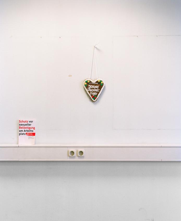 """Liebesbeweis in Form eines Herzlebkuchens und ein Radgeber """"Schutz vor sexueller Belästigung am Arbeitsplatz"""". In einem Büro des ehemaligen Hängeversandlagers."""