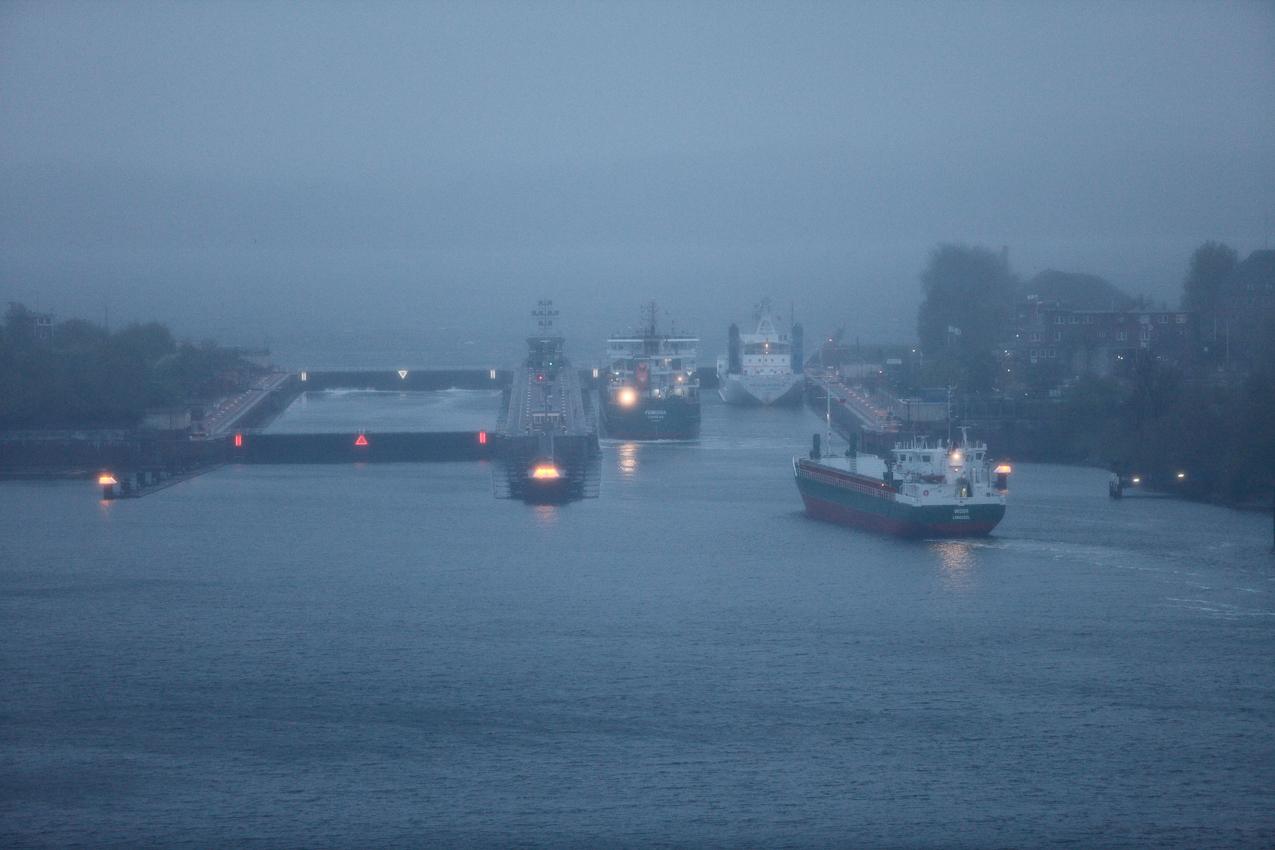 """Die Neuen Schleusen in Kiel-Holtenau in der Morgendämmerung von der alten Holtenauer Hochbrücke aus fotografiert. MS """"Widor"""" lauft als letztes Fahrzeug aus dem Kanal in die Schleuse ein, MS """"Fembria"""" und MS """"Neerlandic"""" liegen bereits in der Sudkammer. Das Signal (ein Grün) weist der """"Widor"""" die Mittelmauer zum Festmachen zu. Die Nordkammer ist leer, beide Tore sind geschlossen. Starker Regen behindert die Sicht auf die Kieler Förde, das gegenüberliegende Ostufer der Förde ist nur zu erahnen."""