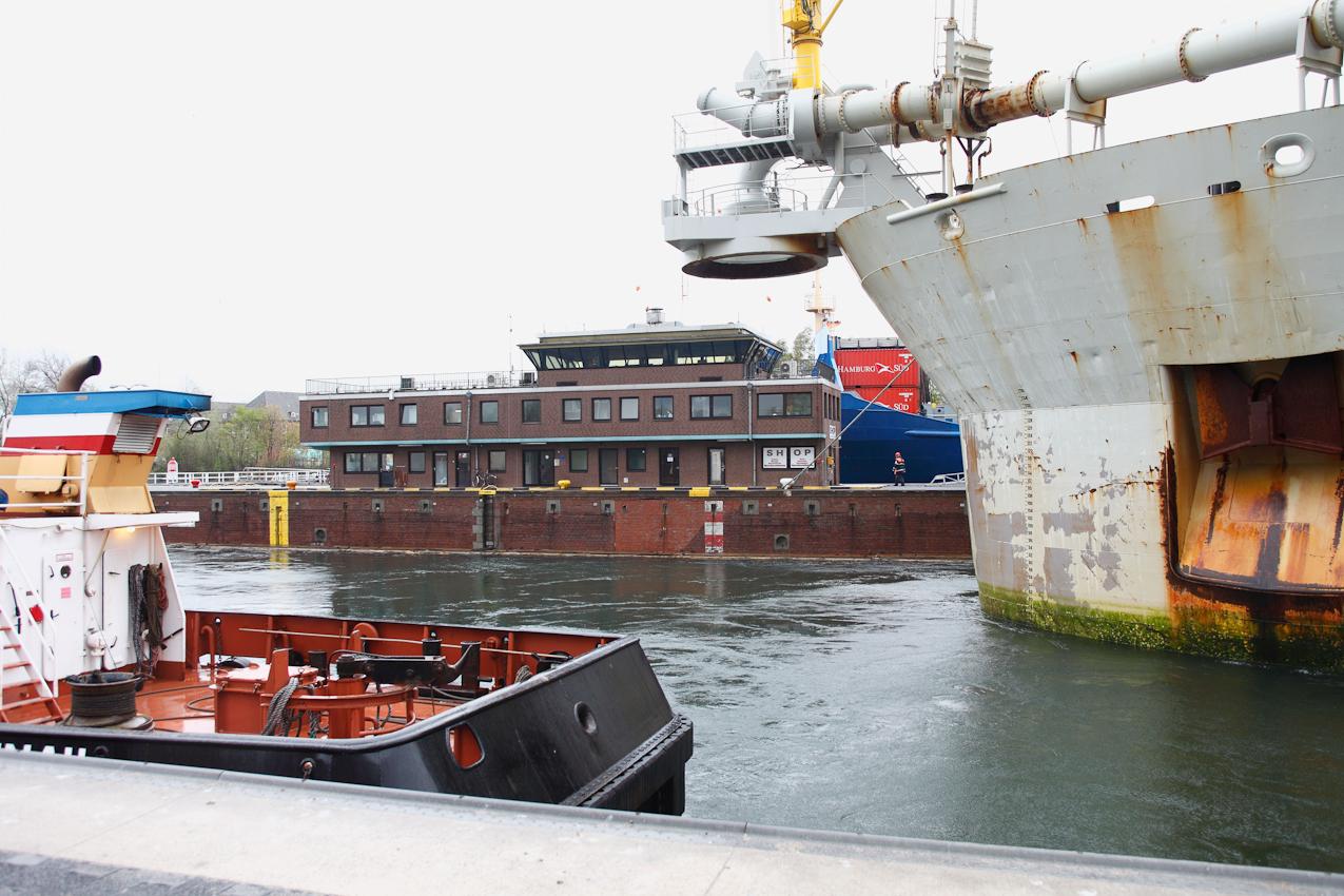 """Der Saugbagger """"Gerardus Mercator"""" und der Schlepper """"Holtenau"""" liegen in der Nordkammer der Kieler Schleuse und warten auf den Wasserstandsausgleich. Das Gebäude in der Mitte zwischen den beiden Kammern ist der Leitstand, auf dem die Schleusenmeister arbeiten. Dahinter befindet sich die Südkammer in der ein Containerschiff liegt."""