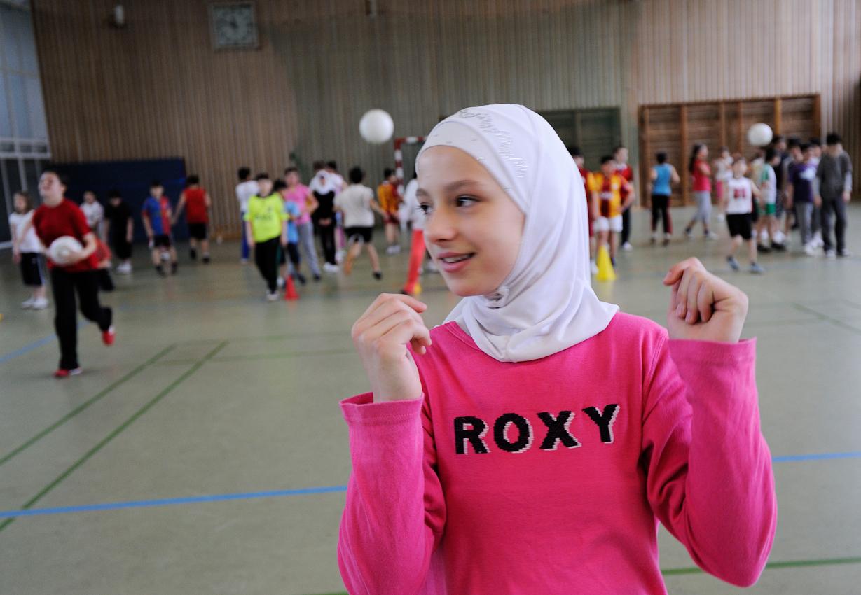 Schülerin mit Kopftuch beim Sportunterricht.