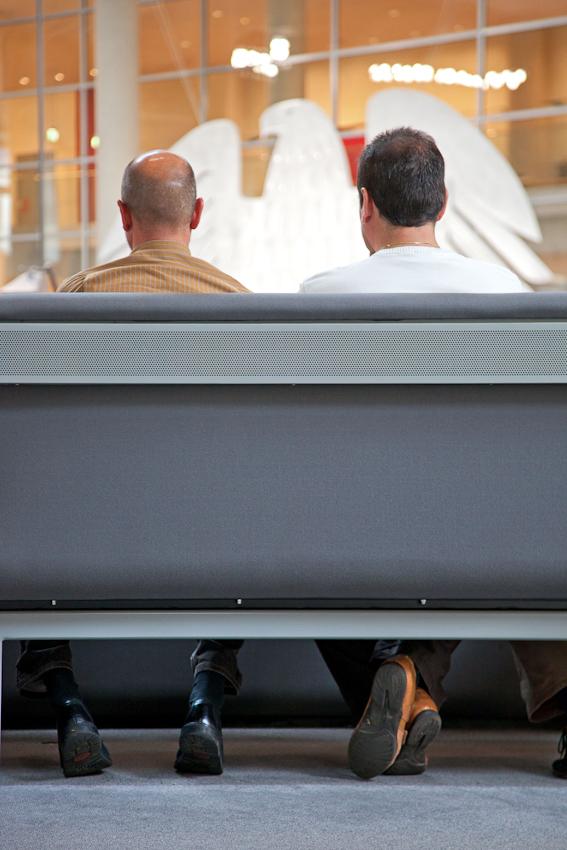 Reichstag, Plenarsaal. Zwei Besucher, auf einer Bank sitzend, blicken in den Plenarsaal.