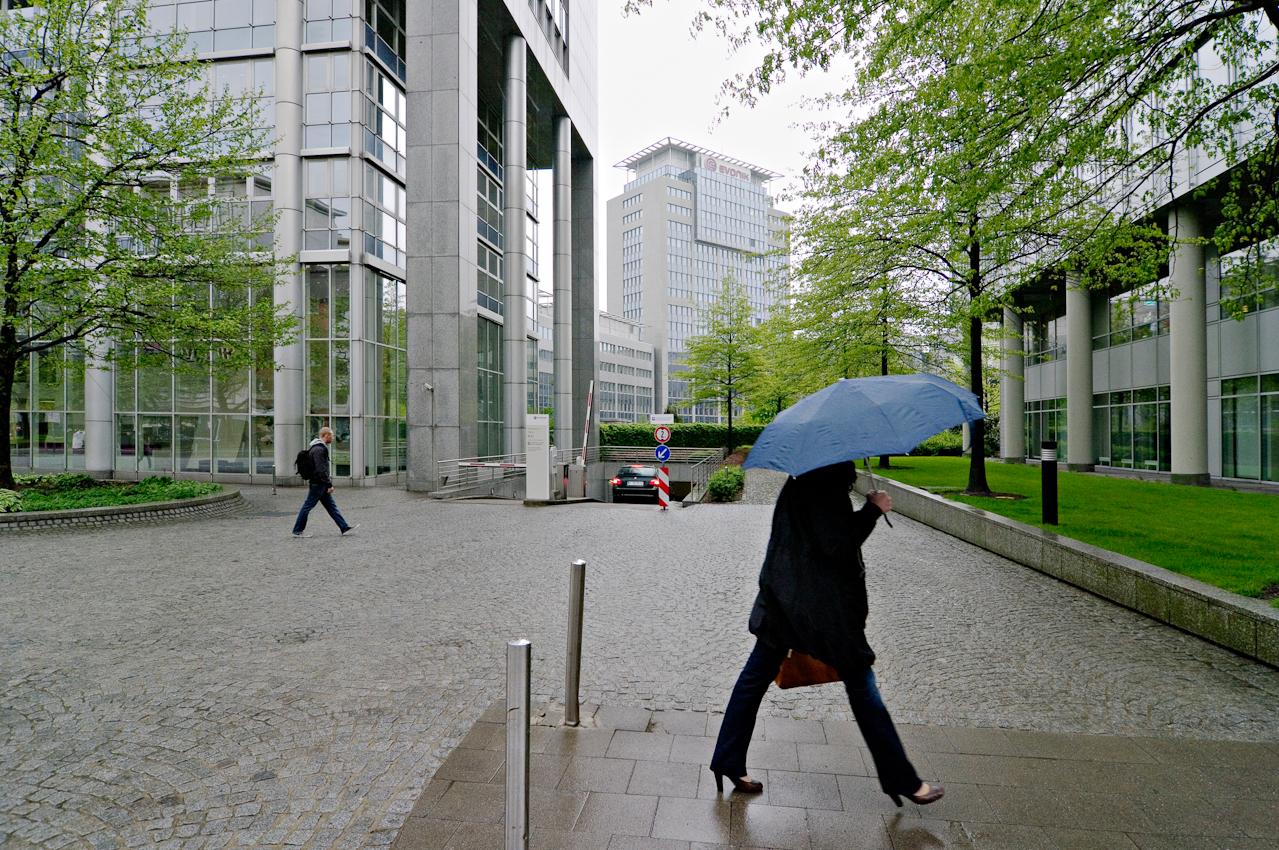 """Morgendliche Bürolandschaft mit Büro-Arbeitern vor der Kulisse des Gebäudekomplex """"Rellinghaus"""" von Evonik Industries AG."""