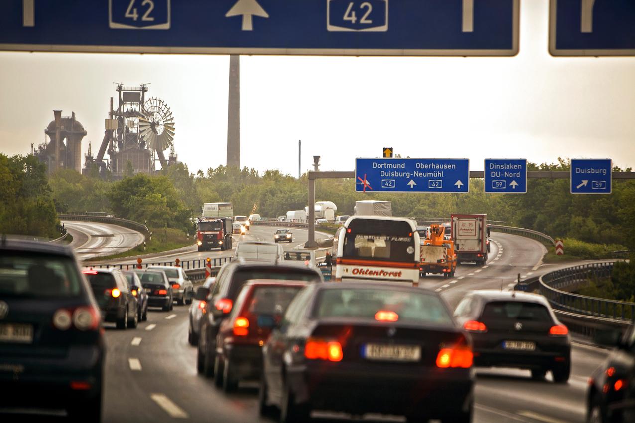 Stau auf der Autobahn A42 Emscherschnellweg zwischen Duisburg-Beeck und Duisburg-Nord im Autobahnkreuz zur Autobahn A59. Links die Hochöfen des ehemaligen Thyssen-Hüttenwerks Duisburg-Meiderich, das mit der Internationalen Bauausstellung IBA Emscher Park zum nachts illuminierten Landschaftspark Duisburg-Nord umgestaltet worden ist.