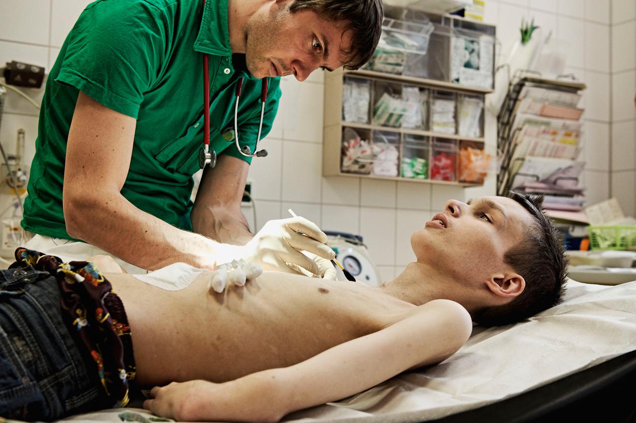 """Dr. Sebastian Werner und Christian während einer Kontrolluntersuchung seiner """"Hickman""""-Katheder und PEG-Sonde nach einer Knochenmark-Transplantation."""