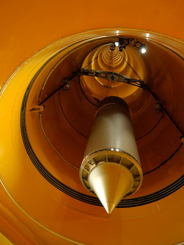 Die Fallkapsel hängt im unteren Bereich der Fallröhre. Nach dem Abwurf wurde sie aus dem Auffangbehälter gezogen und in diese Position gebracht. Jetzt kann der Auffangbehälter zur Seite geschwenkt werden und danach wird die Fallkapsel im Zentrum des Turmes abgesetzt.