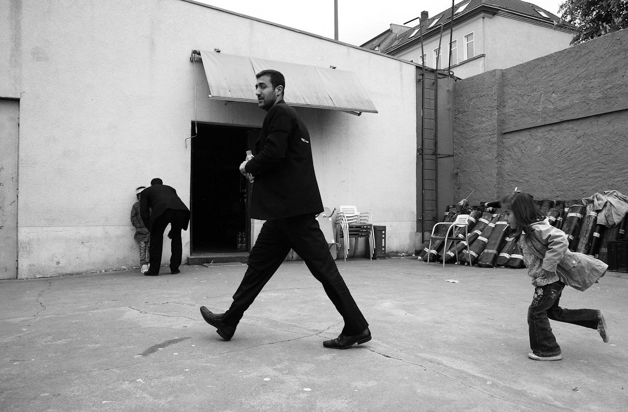 Auf dem Hof der Takva-Moschee in Leipzig. Vorne im Bild sieht man einen jungen Mann, vermutlich den Vater, wie er in Richtung der Gebetsräume geht, während ihm ein kleines Mädchen folgt. Im Hintergrund erkennt man die Tür zum Gemeinderaum der Moschee, in welchem eine Küche untergebracht ist und in dem das soziale Leben stattfindet. Links vor der Tür sieht man einen zweiten Mann, ebenfalls mit einem kleinem Madchen, mit dem er sich unterhält.