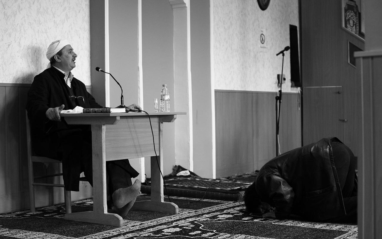 Der Imam spricht die Predigt (khutba) in der Takva-Moschee Leipzig, welche dem Freitagsgebet vorausgeht. Rechts verrichtet ein Gläubiger sein Gebet, wie es nach dem Betreten des Raumes vorgeschrieben ist.
