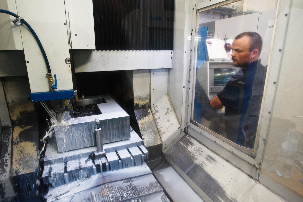 Thomas Gerteisen, Mitarbeiter der Firma Color Metal, bedient eine mehrachsige CNC-Fräse die gerade aus einem Block Metall den Rohling für eine Präzisionsdruckgussform herstellt. Der Bohrkopf schafft bis zu 14.000 Umdrehungen pro Minute, dennoch dauert die Bearbeitung eines solchen Blockes oft einen ganzen Tag oder sogar langer. Heitersheim im Markgräflerland am 7. Mai 2010 um 13:43.