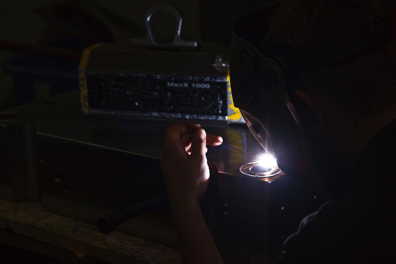 Ein Mitarbeiter der Firma Color Metal schweißt in der Werkshalle der Firma einen Ring in einen zuvor von einer CNC-Fräse bearbeiteten Metallblock. Heitersheim im Markgräflerland am 7. Mai 2010 um 13:30.