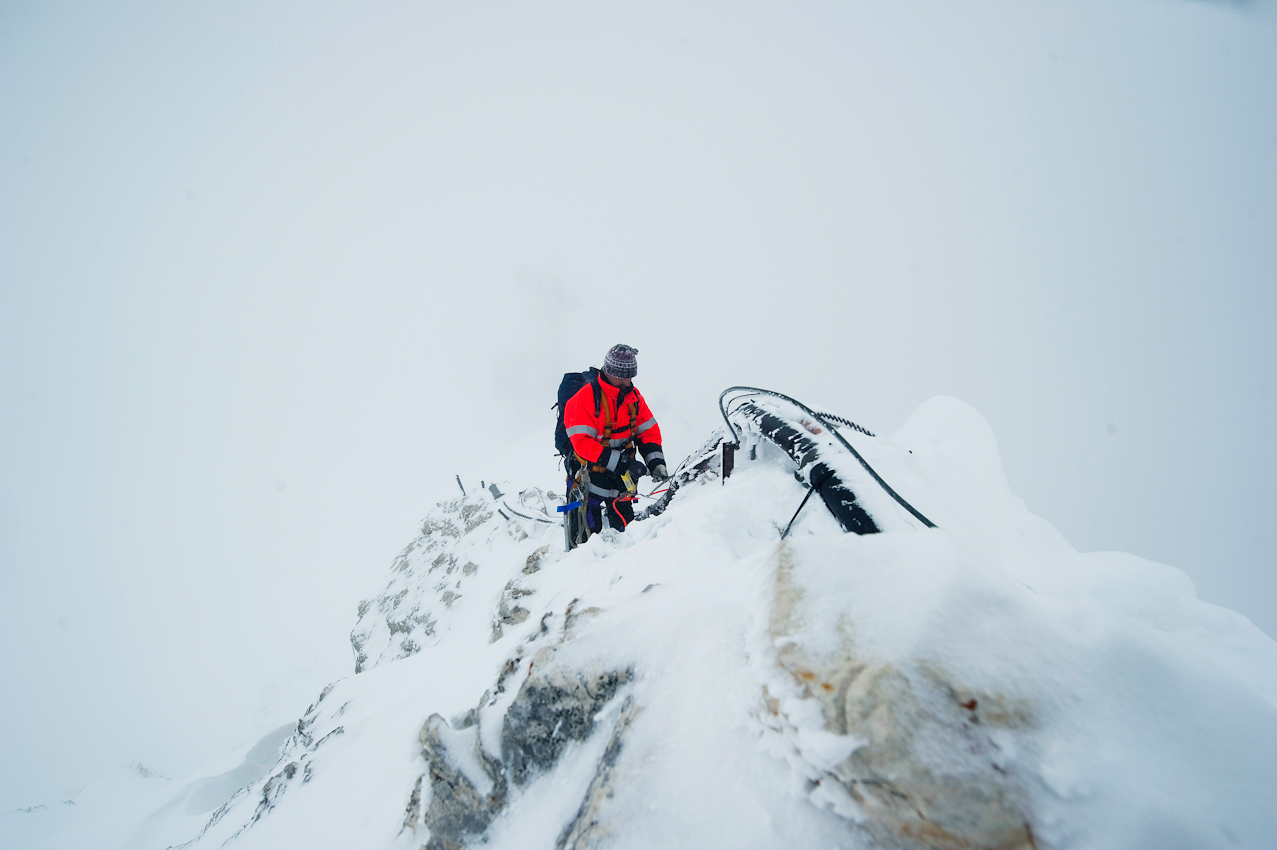 Am Grat vom Zugspitzgipfel zum Zugspitzeck liegt noch hüfttief Schnee. Der Wind bläst die Eiskristalle wie Nadeln ins Gesicht. Trotzdem muss das Hochspannungskabel kontrolliert und gesichert werden.