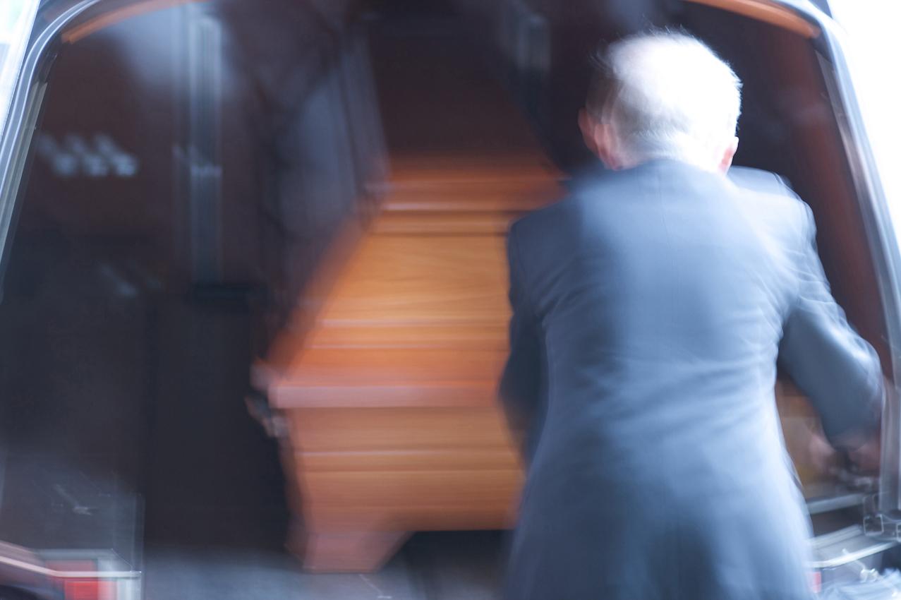 Hier wird ein Sarg zur Überführung ins Krematorium in das Bestattungsfahrzeug geschoben.