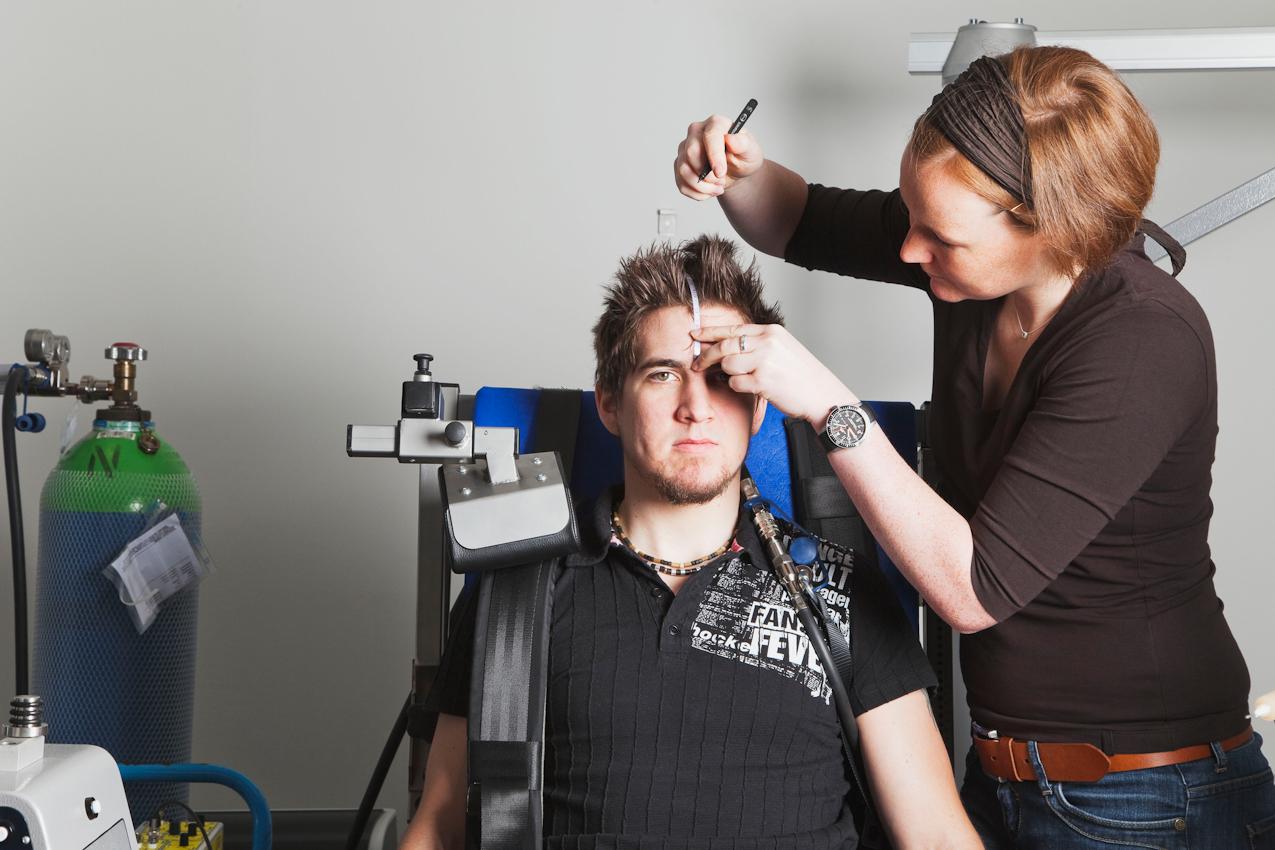 Die Wissenschaftlerin Vera Brummer (links im Bild) vermisst den Kopf des Probanden Fabian Schurg und markiert die Position der Stirnelektroden für den korrekten Sitz der EEG-Kappe, welche die Hirnströme aufzeichnen soll.
