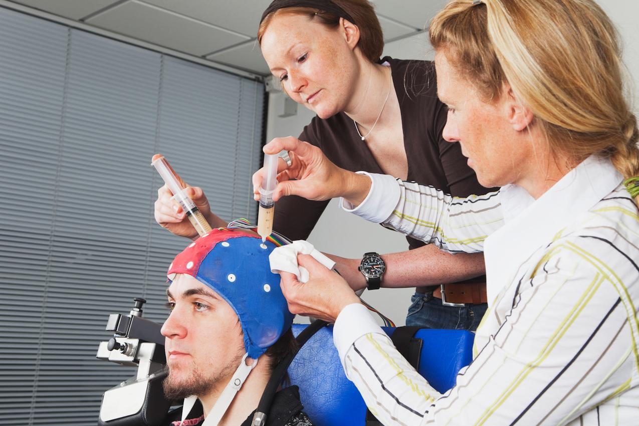 Wissenschaftlerin Vera Brummer (Bildmitte) injeziert Elektrodengel in die EEG-Kappe. Diese sorgt für eine Verbindung zwischen Elektroden und Kopfhaut zur besseren Aufzeichnung der Gehirnströme des Probanden Fabian Schurg. Die Fotografin Gaby Wojciech (rechts im Bild) assistiert dabei.
