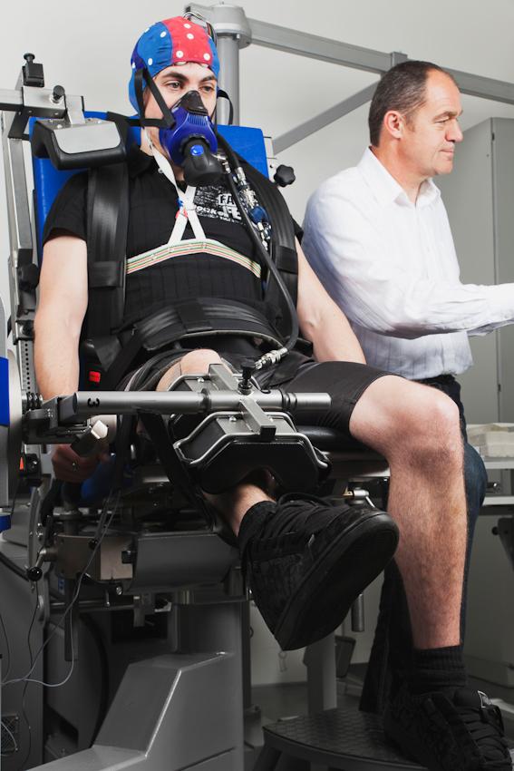 Proband Fabian Schurg (links) trainiert das rechte Bein gegen den Widerstand der Kraftmaschine. Über die Atemmaske atmet er sauerstoffarme Luft, während die Beinelektroden die Muskelaktivität messen und die EEG-Kappe die Hirnströme aufzeichnet. Laborleiter Dr. Axel Knicker (rechts) überwacht die Datenaufnahme.