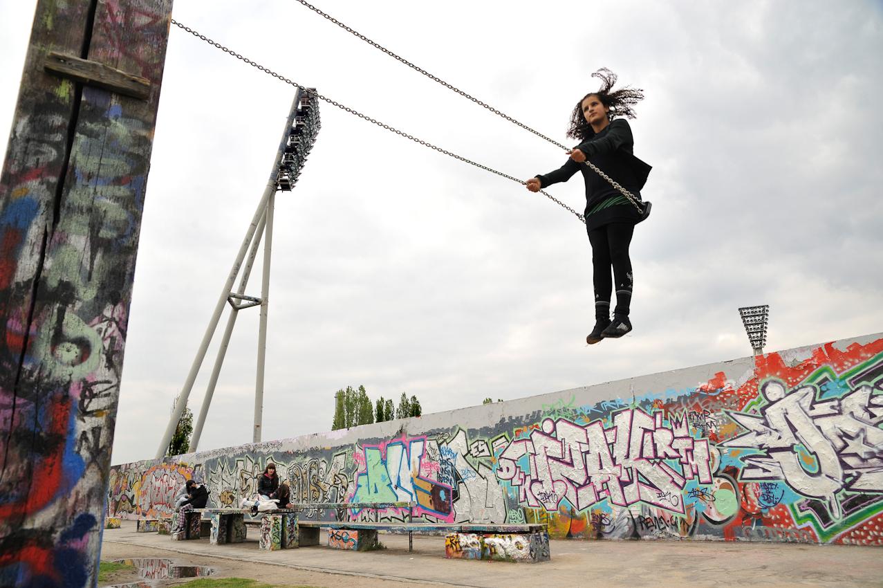 Eine Jugendliche auf einer Schaukel, mit Graffiti besprühte innere Mauer (zur DDR-Seite errichtete Mauer der ehem. Grenzanlagen), Flutlichtmasten des Cantian-Stadions.